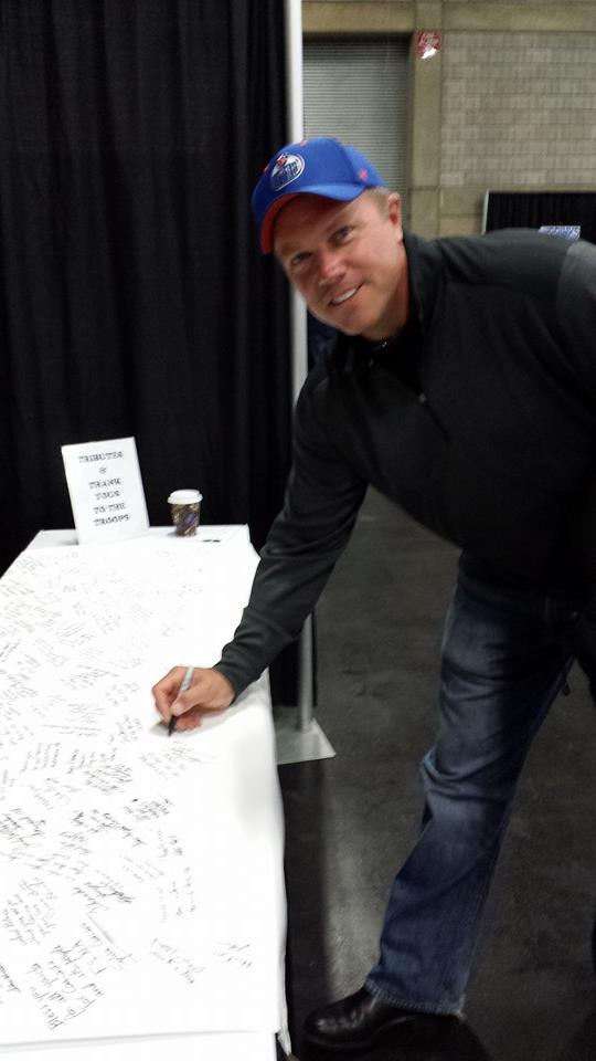 """Adam Baldwin signing the """"Support Our Troops"""" banner at the CHAS Touch History Expo."""